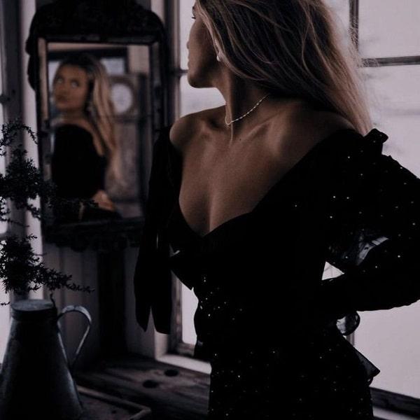 Elegantna plava žena iz fantazije ogleda se u ogledalu