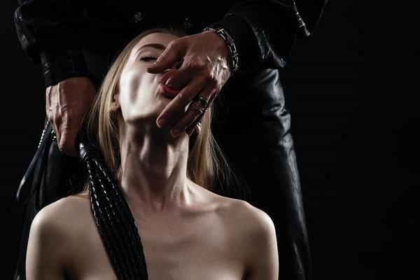 Potlačenost plave devojke muškarcu koji joj stavlja prst u usta